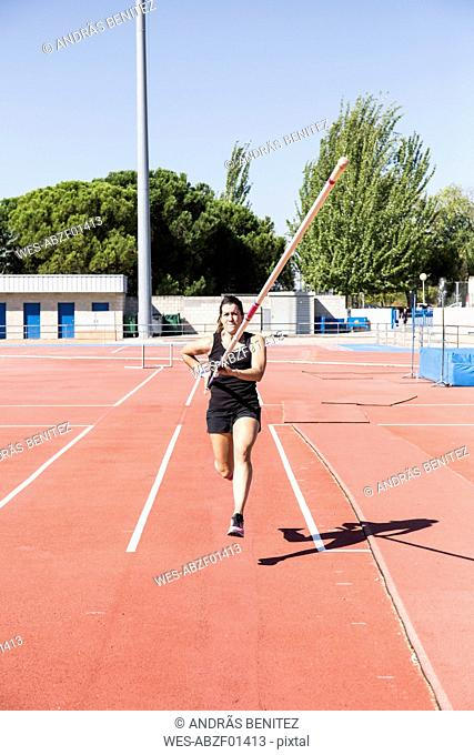 Female pole vaulter running with pole