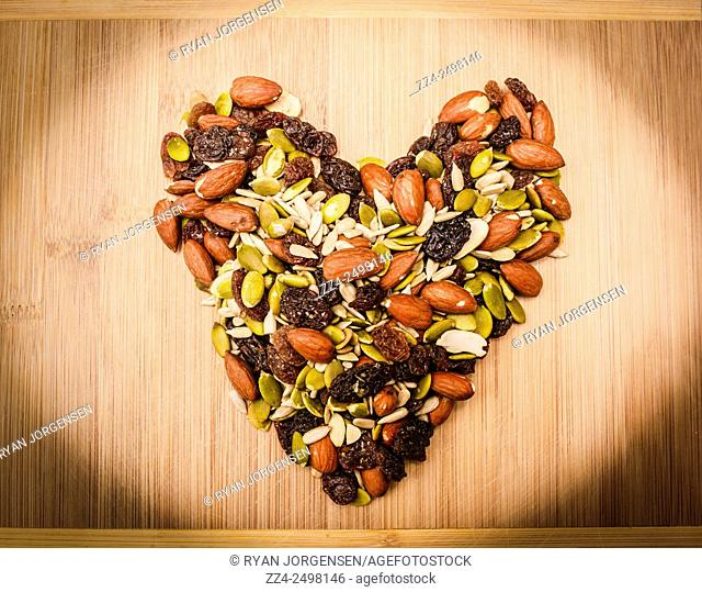 Still life food photo on a heart made of sunflower kernels, almonds, pepitas, raisins and sultanas. Natural ingredients love