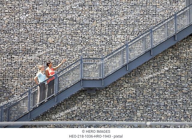Businesswomen giving directions on staircase