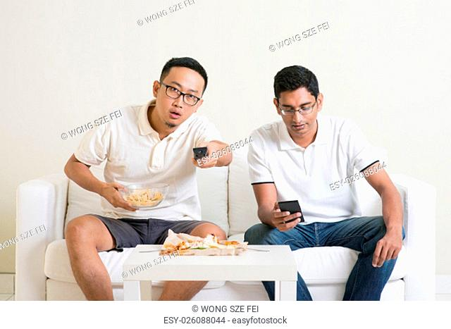 Friendship, technology and home concept. Two male friends with remote control and junk food at home