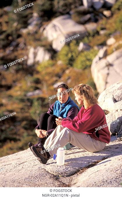 Two Female Hikers Sitting On A Rock And Resting Together