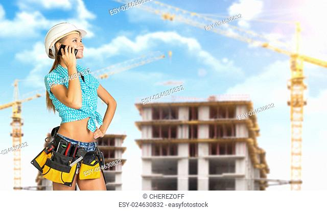 Woman in helmet and tool belt with different tools, talking on phone. Construction site in background