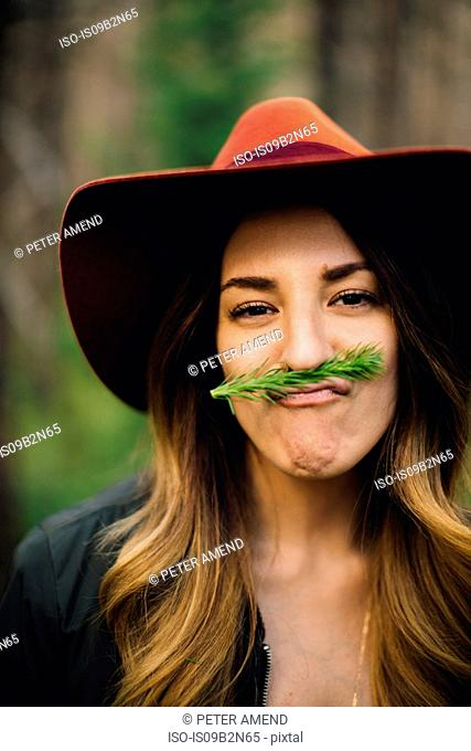 Portrait of woman with foliage moustache pulling face, Rocky Mountain National Park, Colorado, USA