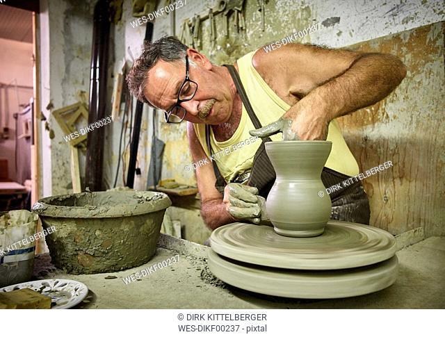 Potter in workshop working on earthenware jug