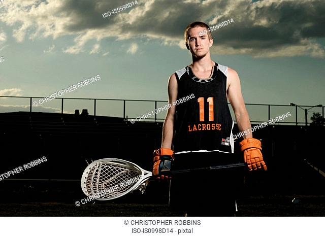 Young sportsman holding lacrosse stick in sportsground