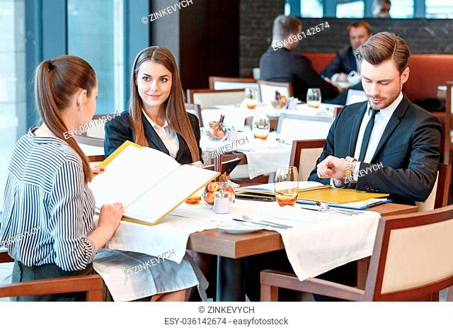 Need to control timing of the meeting. Businesswomen at the lunch table look at other and their male colleague looks at the watch to check the time