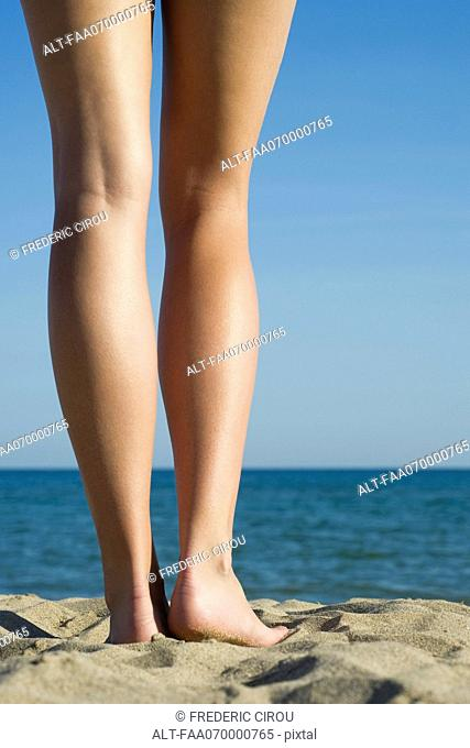 Young woman standing on beach, close-up of bare legs