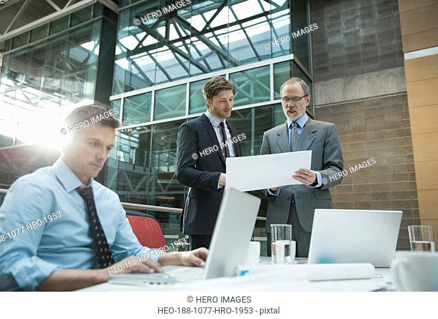 Businessmen reviewing paperwork in conference room