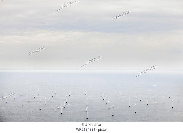 Aerial view of windmills in sea against sky