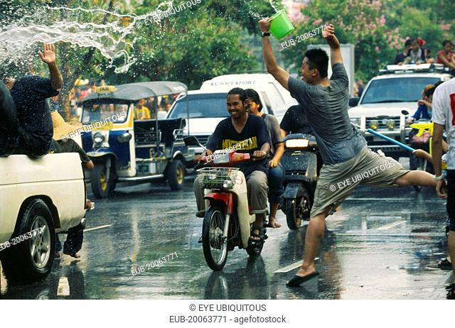 Songkran aka Thai New Year. Revellers in a pickup truck attempting to catch some of the water thrown at them over the heads of motorcyclists