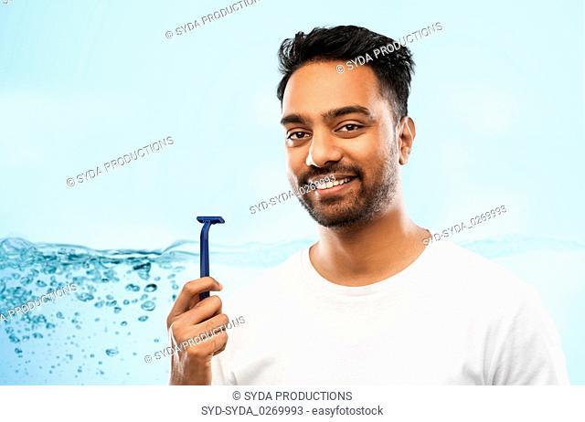 indian man shaving beard with razor blade