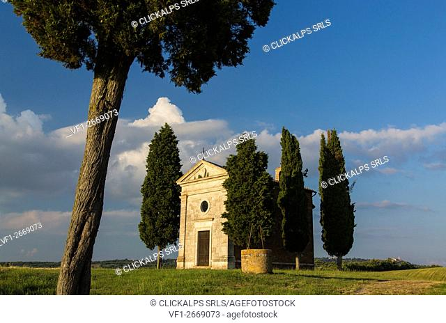 Surrounded by typical Tuscan cypress trees, the chapel of Our Lady of Vitaleta,tuscany,italy, and in the background the town of Pienza
