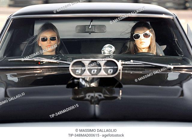 Two women sitting on vintage car