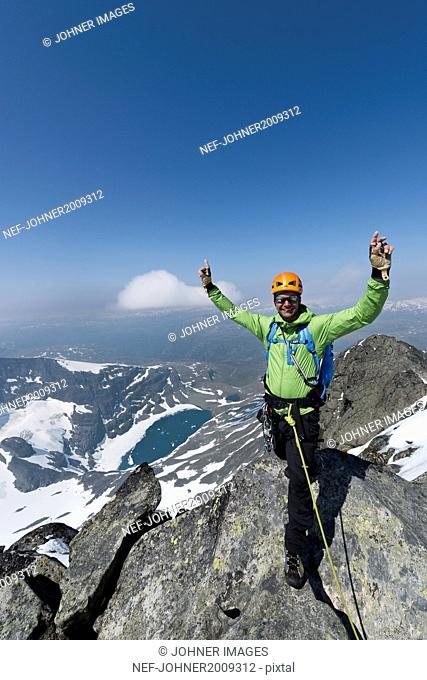 Smiling man on top of mountain