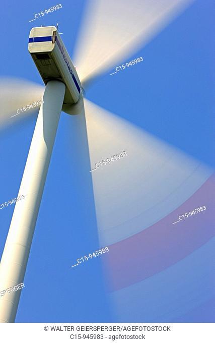 Spinning Wind turbine generator against blue sky