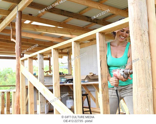 Smiling woman drilling in plank in house under construction