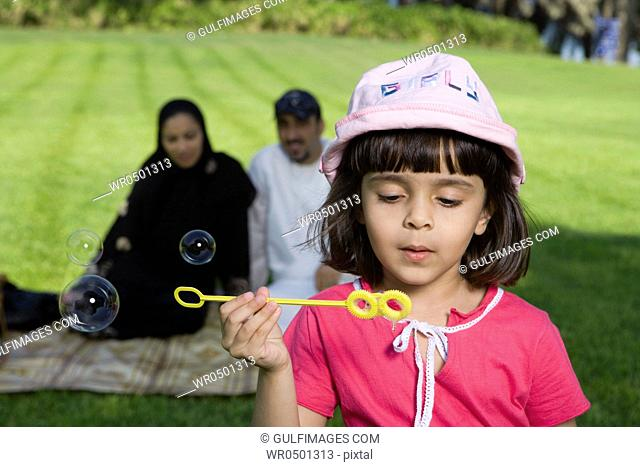 Girl holding bubble wand while parents sitting in background