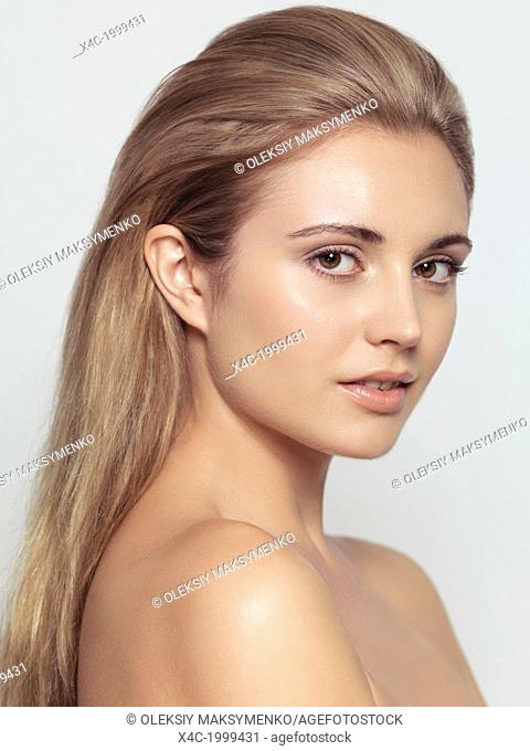 Beauty portrait of young woman with light brown hair with natural clean makeup and contemporary hairstyle isolated on light gray background