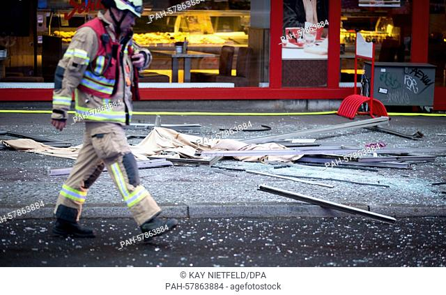 A fire fighter walks past glass shards from a building where a fire occurred in Berlin,Germany, 28 April 2015. One person was killed