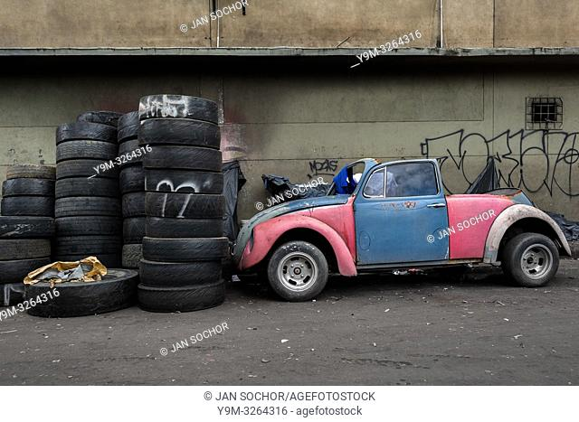 A Volkswagen Beetle car wreck, parked next to a pile of tires, is seen in the street of Barrio Triste, a car mechanics neighborhood in Medellín, Colombia