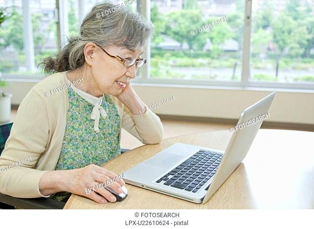 Senior woman using laptop, Kanagawa Prefecture, Honshu, Japan