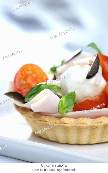 Small tartlets of cured hame, mozzarella and basil