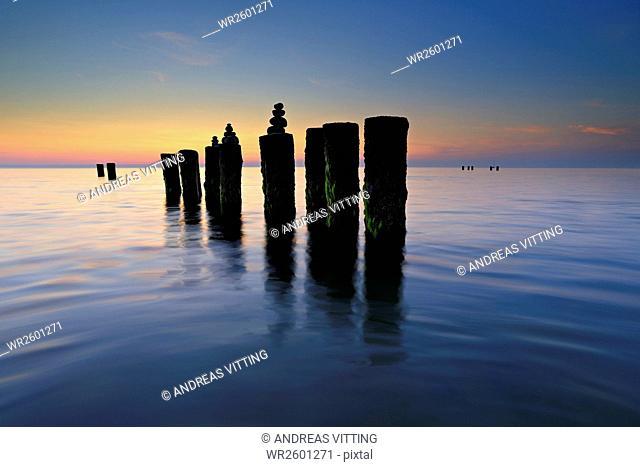 Sunset at west coast, stone pyramids on old groyne, Darß, Baltic Sea, Mecklenburg-Western Pomerania, Germany