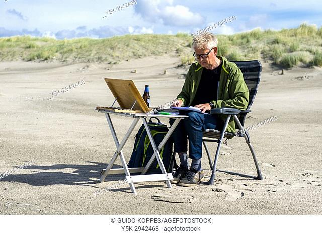 """Hook of Holland, Netherlands. Mature adult male clerck reading his documents, while being """"""""installed"""""""" on the North Sea coastal beach"""