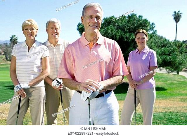 Two mature couples standing on golf course, playing golf, smiling, front view, portrait