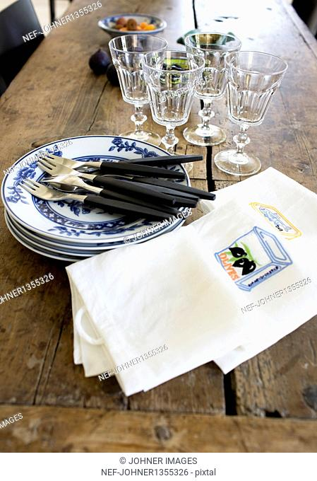 Napkins, crockery and cutlery on wooden table