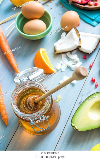 Jar of honey with dipper and fresh ingredients