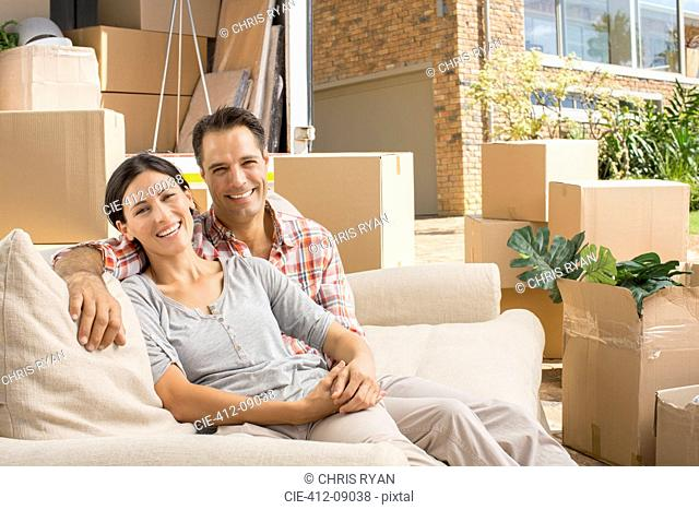 Portrait of smiling couple on sofa near moving van in driveway