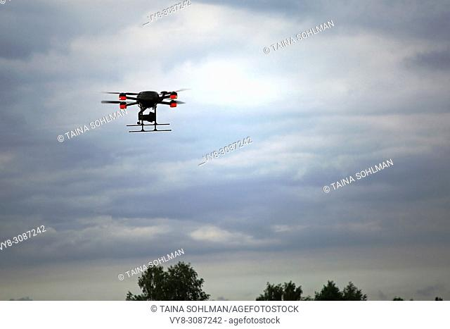 A quadcopter drone in flight over treetops agaist moody sky. Public event in Salo, Finland