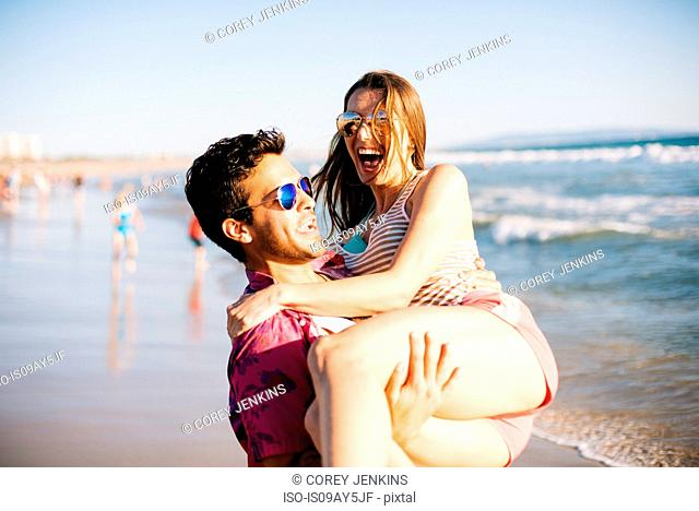 Young man carrying girlfriend on beach, Santa Monica, California, USA