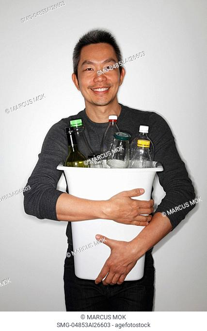 Chinese man holding a bucket of bottles to recycle