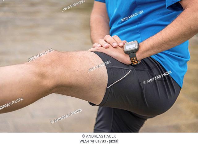Man stretching leg, wearing a smartwatch