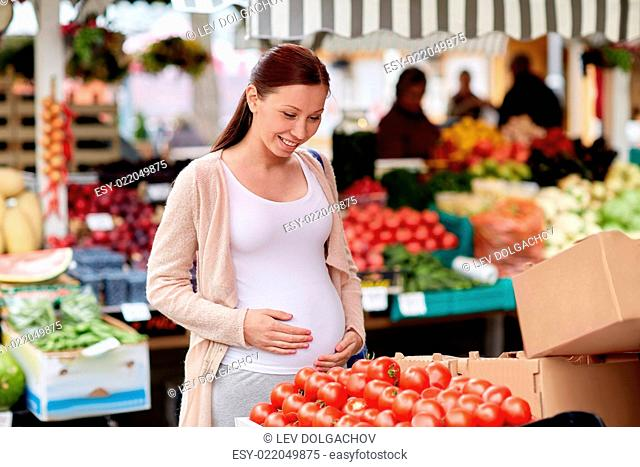 sale, shopping, food, pregnancy and people concept - happy pregnant woman choosing tomatoes at street market
