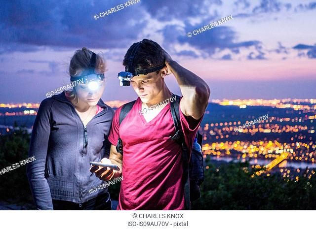 Young couple outdoors at night, wearing head lamps, looking at smartphone