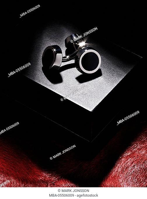 black box, cuff links, red fake fur