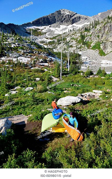 Backpacking couple packs up tent and sleeping bags at Fault Lake in the Selkirk Mountains, Idaho