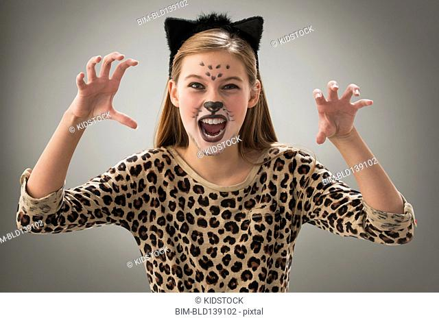 Caucasian girl snarling in leopard costume for Halloween