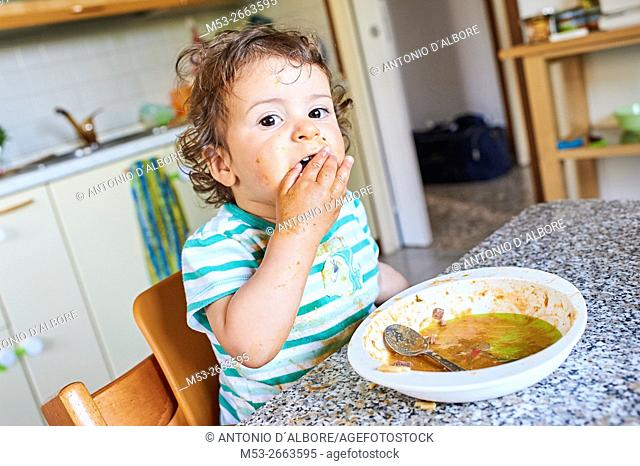 A sixteen months old baby girl learning to eat