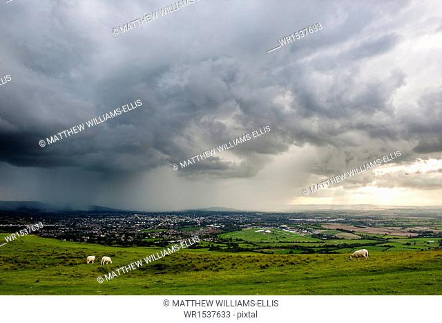 Looking out from Cleve Hill as a storm crosses the Severn Vale, Cheltenham, Gloucestershire, England, United Kingdom, Europe