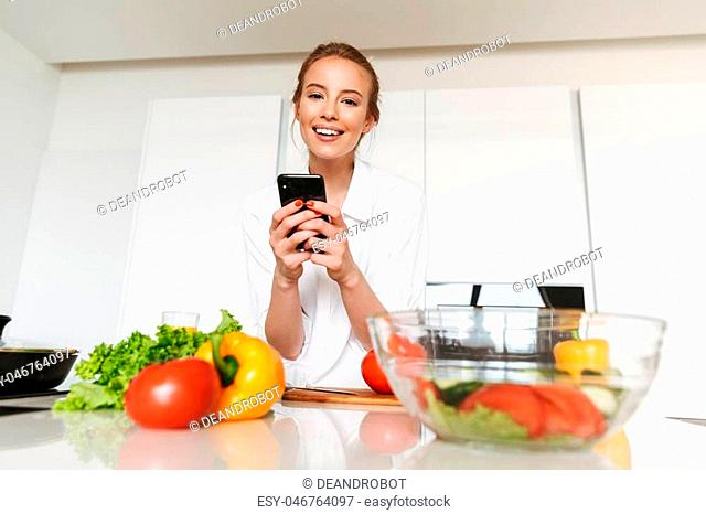 Pretty young woman taking picture with mobile phone while cooking salad on a kitchen