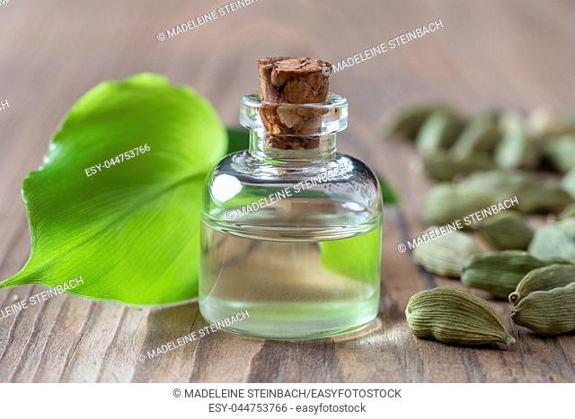 A bottle of essential oil with young cardamon leaves and seeds