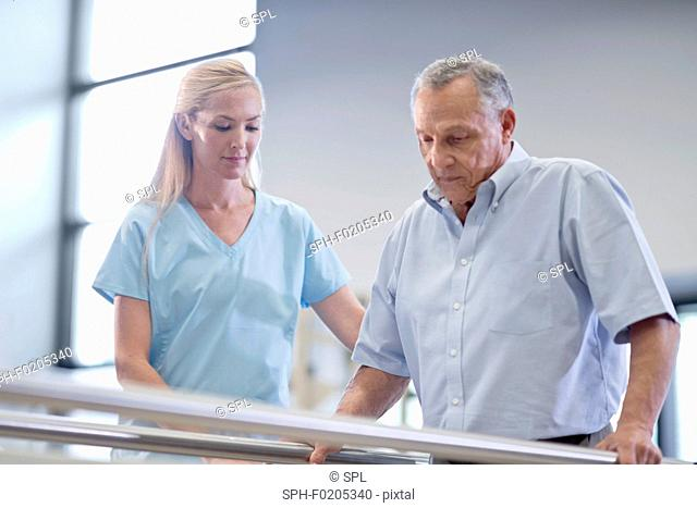 Nurse with senior man using parallel walking bars