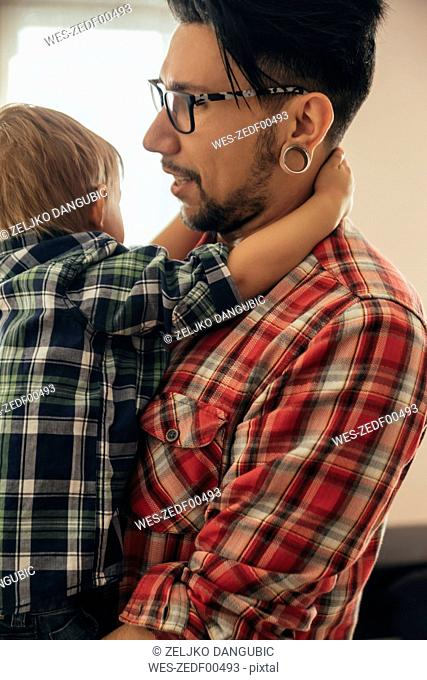 Son hugging father at home