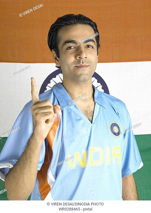 Indian cricket player raising index finger standing in front of flag of India in background MR702A