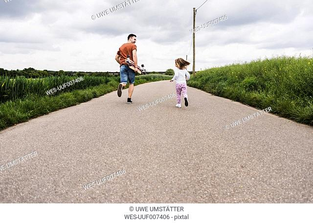 Father with skateboard and daughter running on country lane