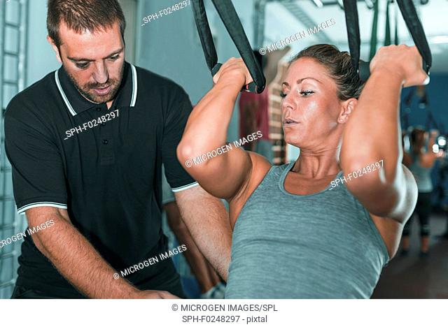 Woman doing TRX workout with personal trainer